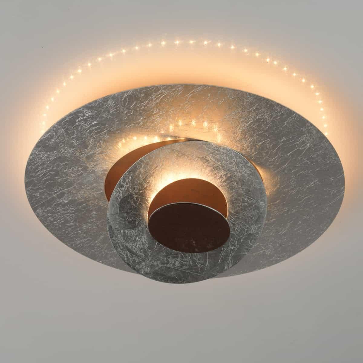 Lustra moderna hi-tech argintie, de la Demarkt, cu LED, cu lumina calda, in tonuri de oranj, pe un fundal gri deschis