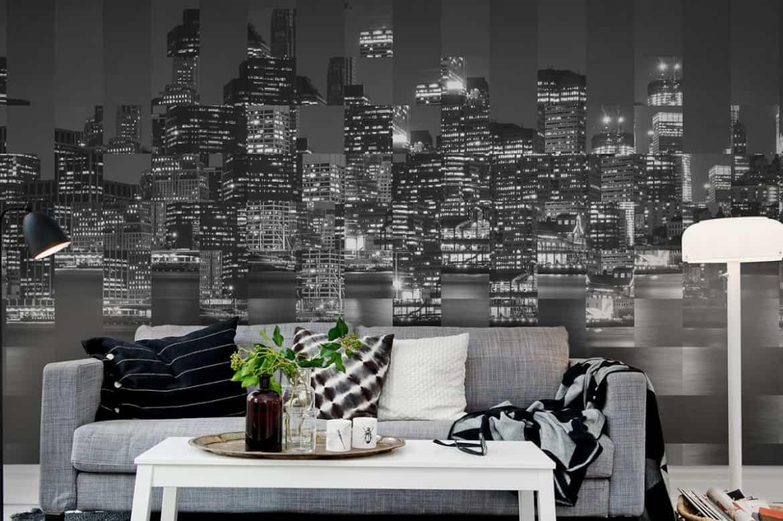 fototapetul new york gri de la rebel walls aplicat peste vopsea lavabila intr-un living modern, cu canapea gri, masa si lampadar albe si obiecte de decor gri, negre si verzi