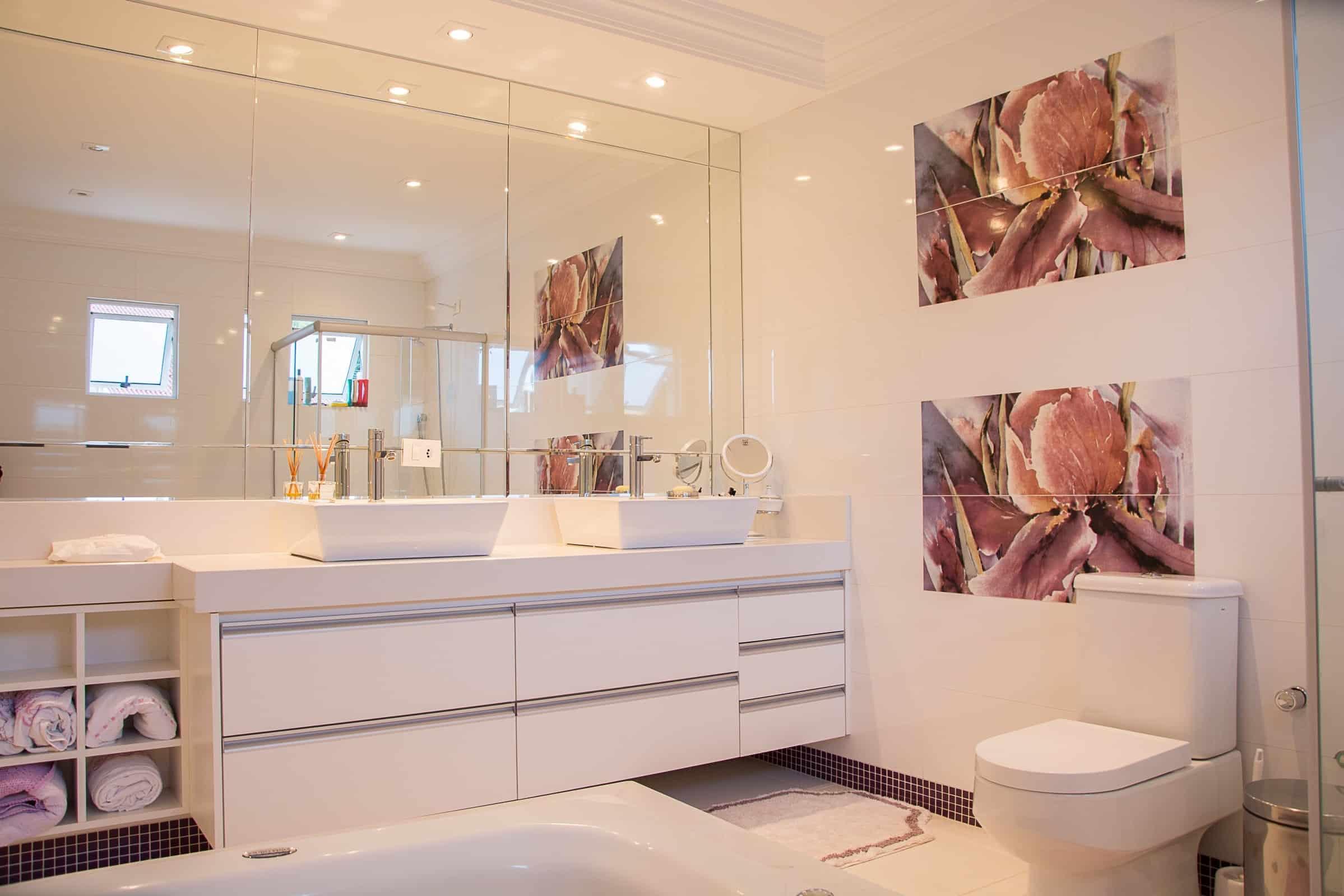 Baie spatioasa, cu mobilier alb, oglinda mare montata direct pe perete, si tablouri cu flori in tonuri de roz