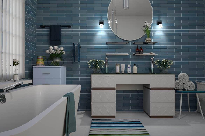 Baie cu gresie, mobila si instalatii sanitare albe si faianta in tonuri de turcoaz, cu un covor multicolor si o oglinda mare, ovala, montata pe perete