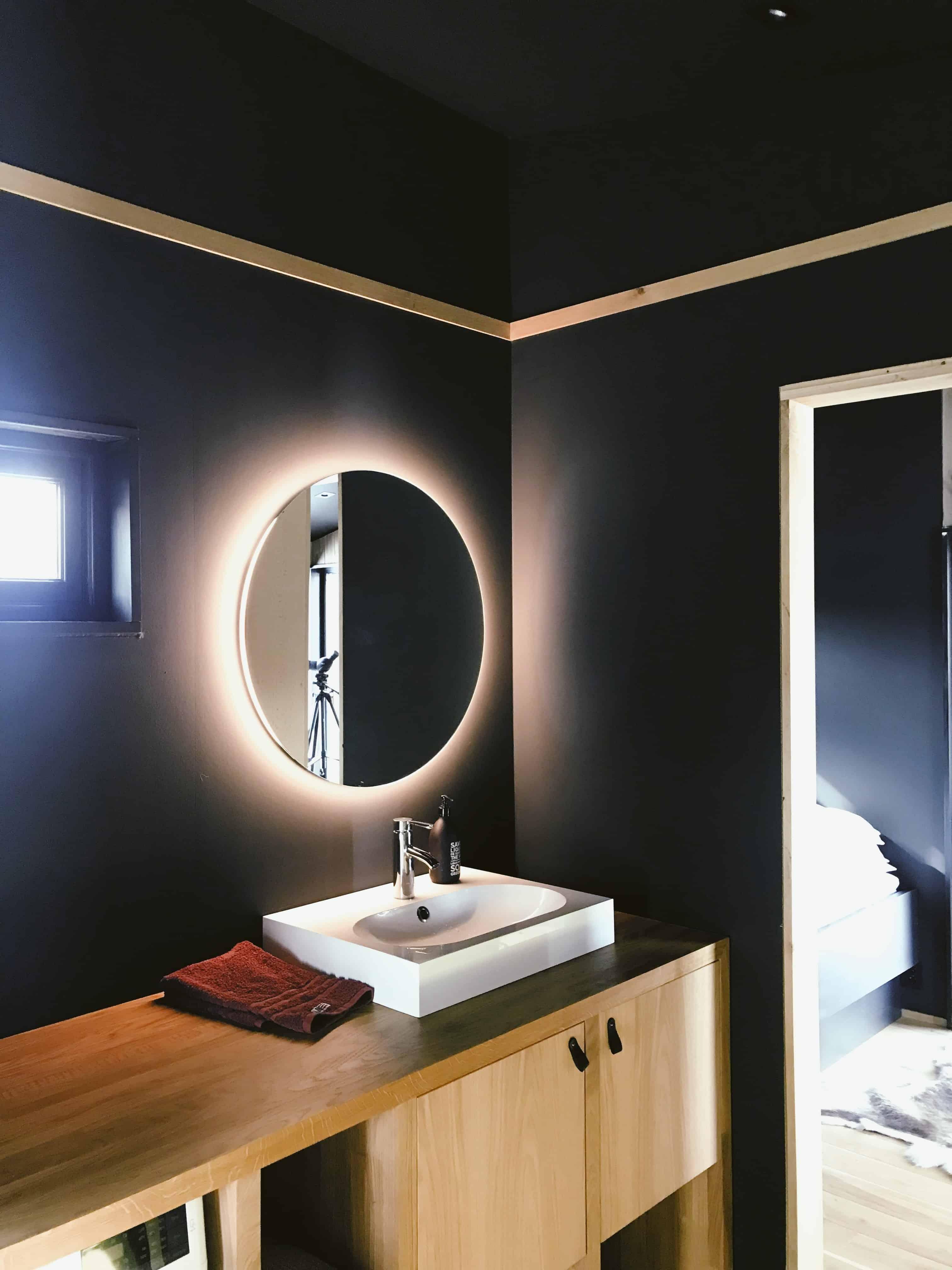 Oglinda de baie ovala montata direct pe perete, intr-o baie cu pereti negri si mobilier maro deschis, din care se vede un colt de dormitor si patul
