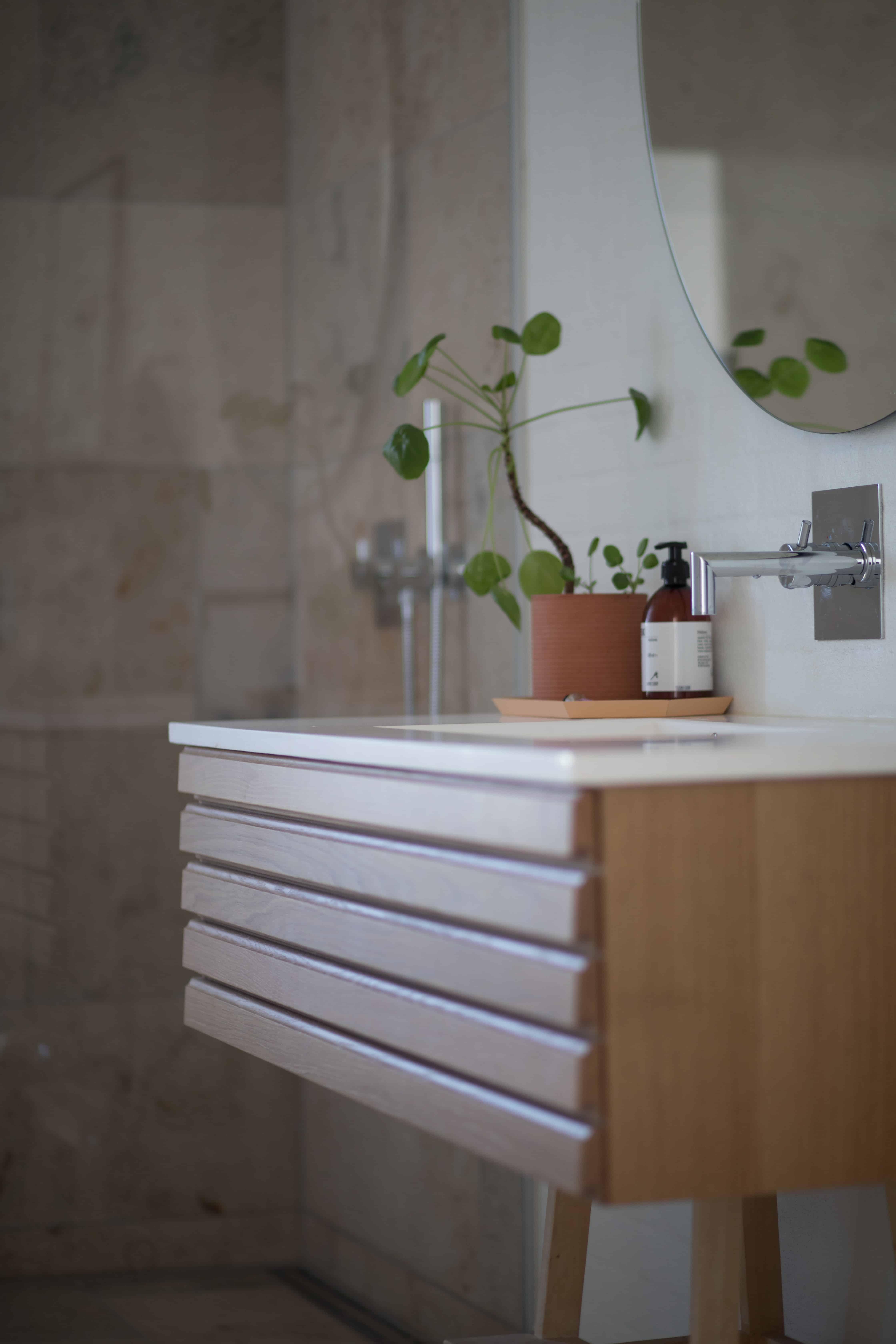 Oglinda mare, simpla, montată direct pe perete, intr-o baie in tonuri deschise, de bej, crem și maro, cu chiuveta suspendata si o planta