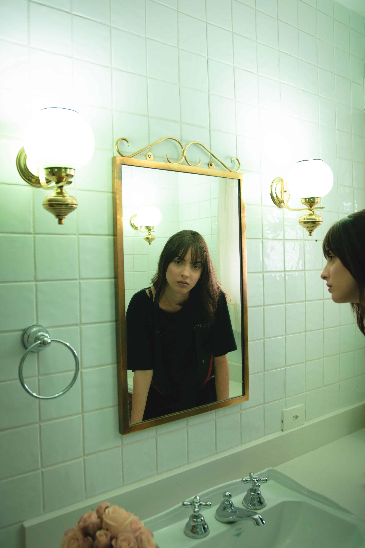 Oglinda in rama aurie, montata direct pe perete, cu o femeie tanara care se reflecta in ea, intr-o baie alba, cu doua aplice pe perete