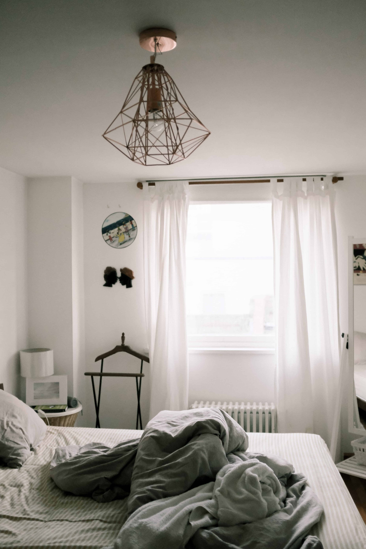 спальня с белыми стенами, с занавесками, кроватью и белым декором и большой, современной, хромированной люстрой