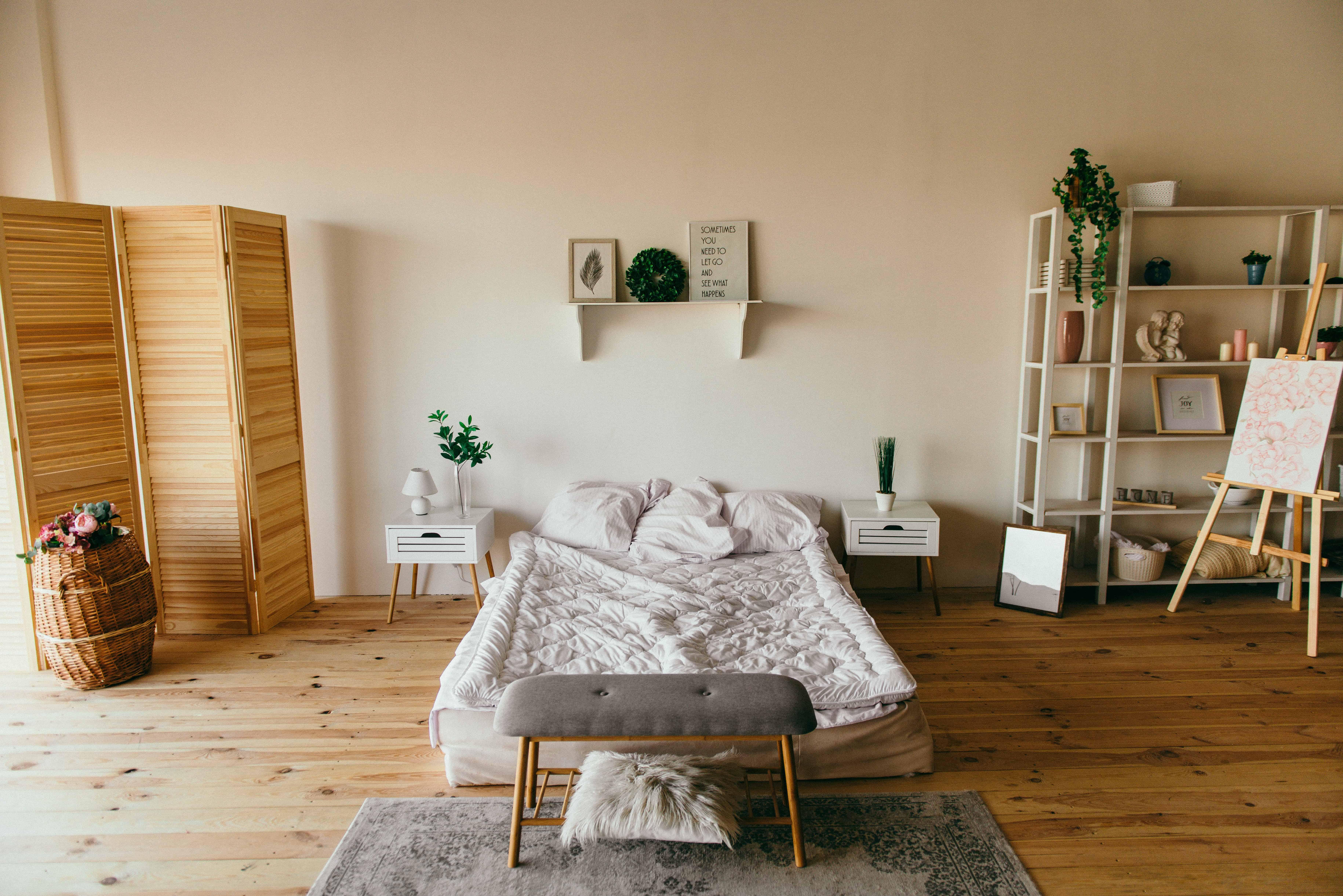 спальня с бежевыми стенами, двуспальная кровать с белым бельем, пол и коричневые элементы декора