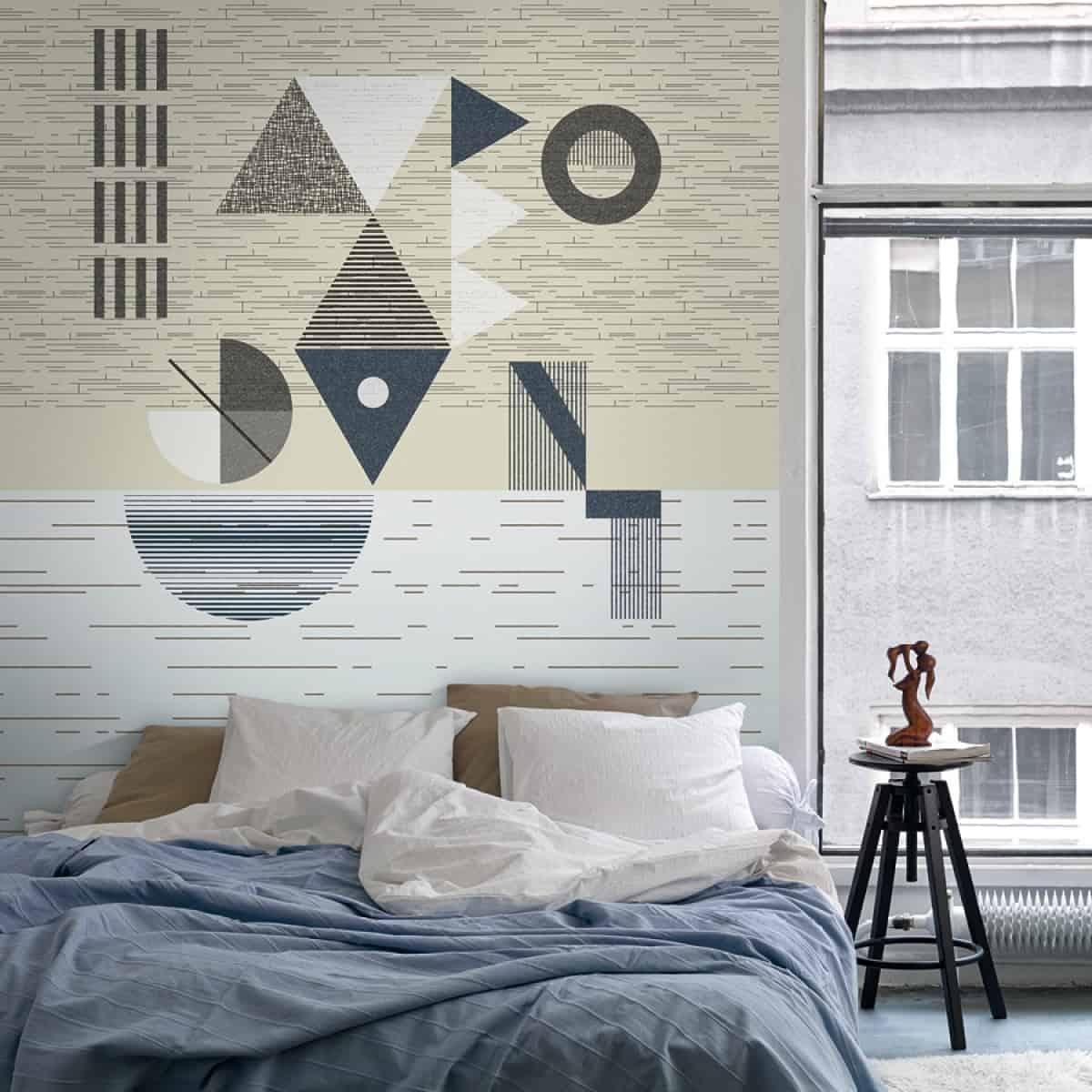 спальня украшена бежевыми обоями, с оттенками синего, серого и коричневого, с белой двуспальной кроватью с сине-черной тумбочкой