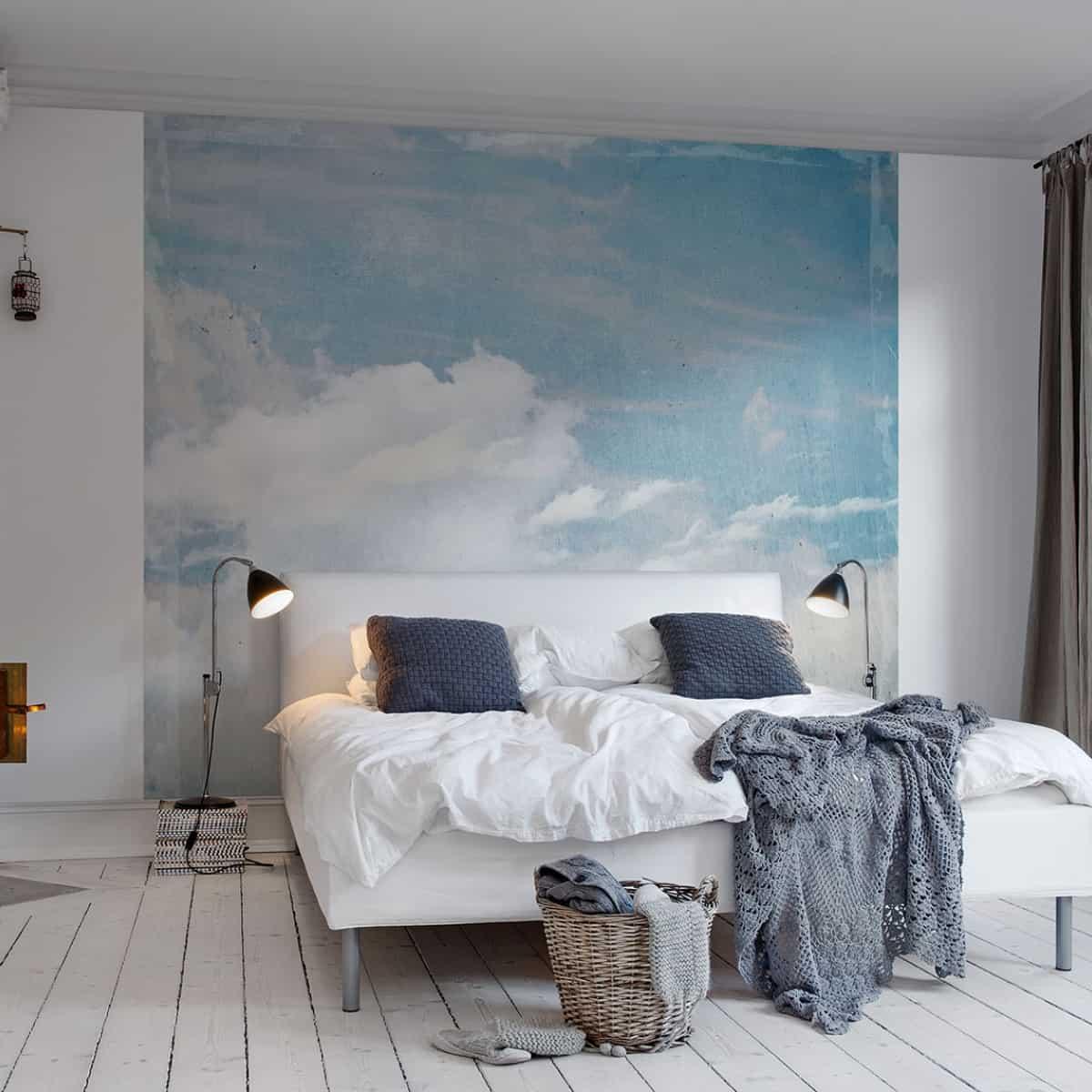 спальня украшена синими и белыми обоями, имитирующими небо с облаками, с двуспальной кроватью с белым и синим бельем и белым полом