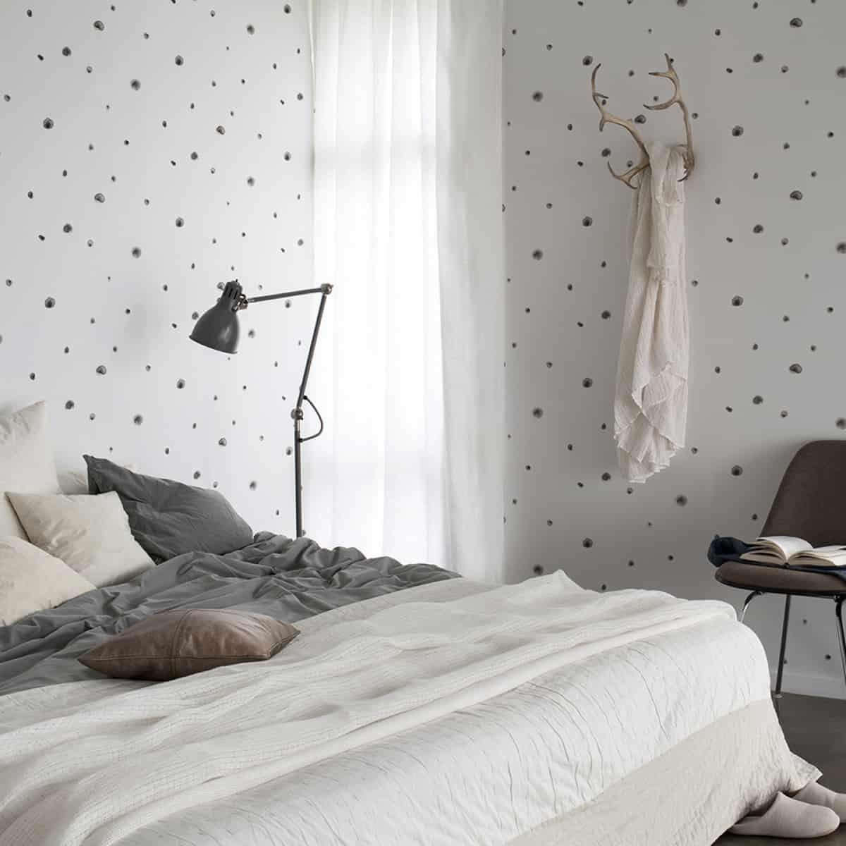 спальня украшена белыми обоями и серых тонов, с бело-серой двуспальной кроватью, серым полом и коричнево-черными элементами декора