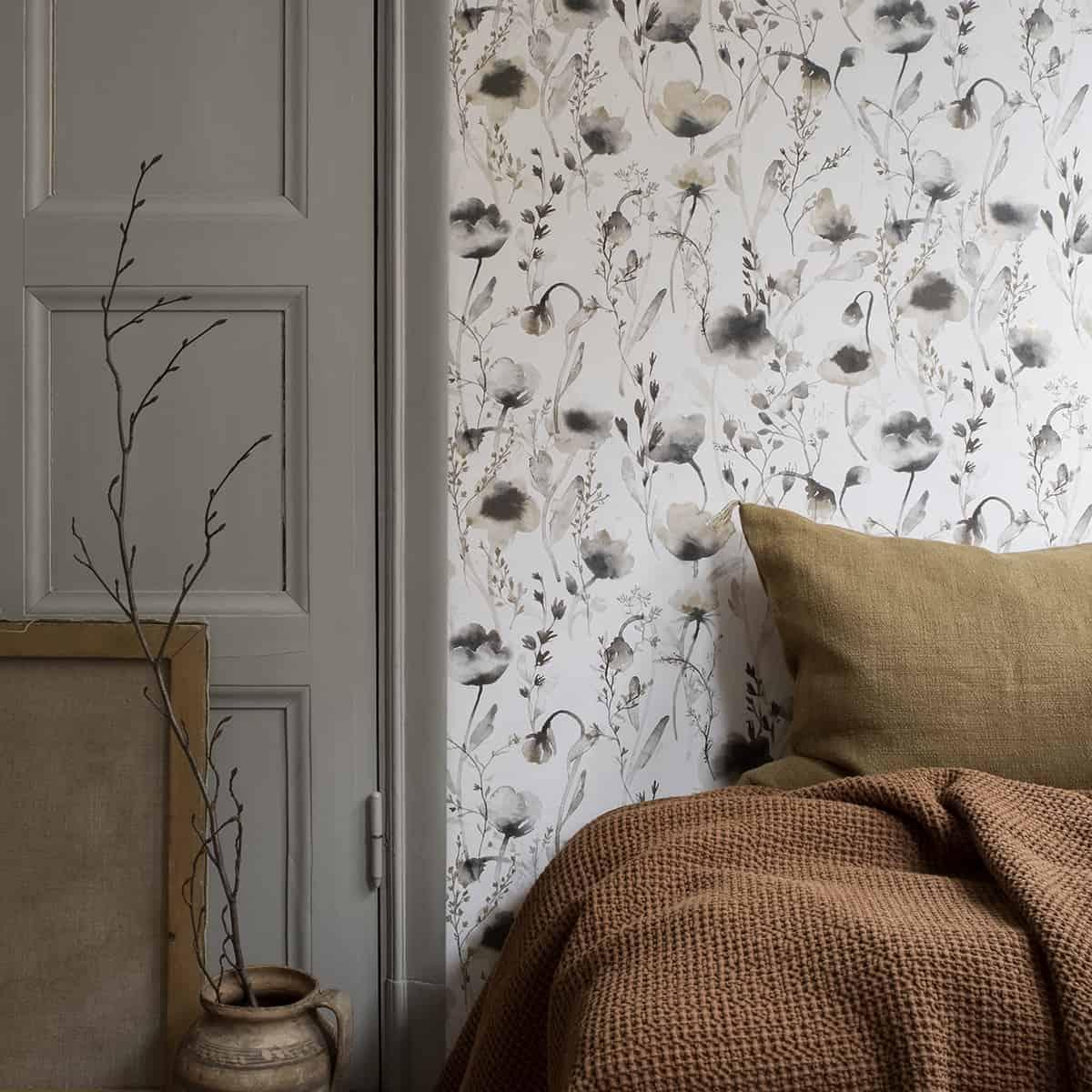 спальня украшена лавандовыми обоями, большой кроватью и декором и серой дверью