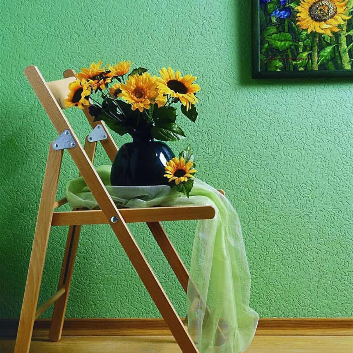 colt de bucatarie cu tapet verde cu scaun maro cu ghiveci cu floarea soarelui si tablou pe perete