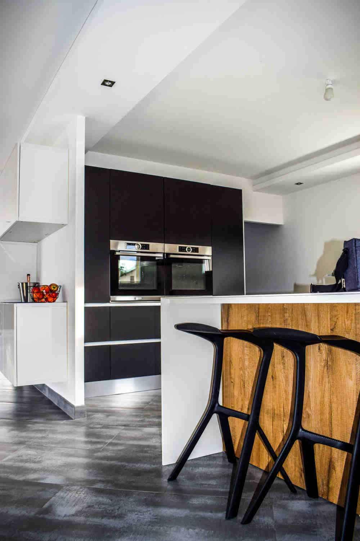 bucatarie moderna cu dulapuri, scaune de culoare maro si electrocasnice incorporabile