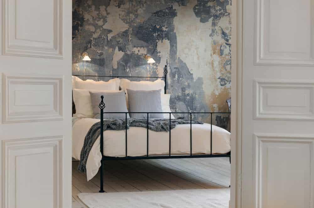 dormitor cu pat pe mijloc si tapet pe perete