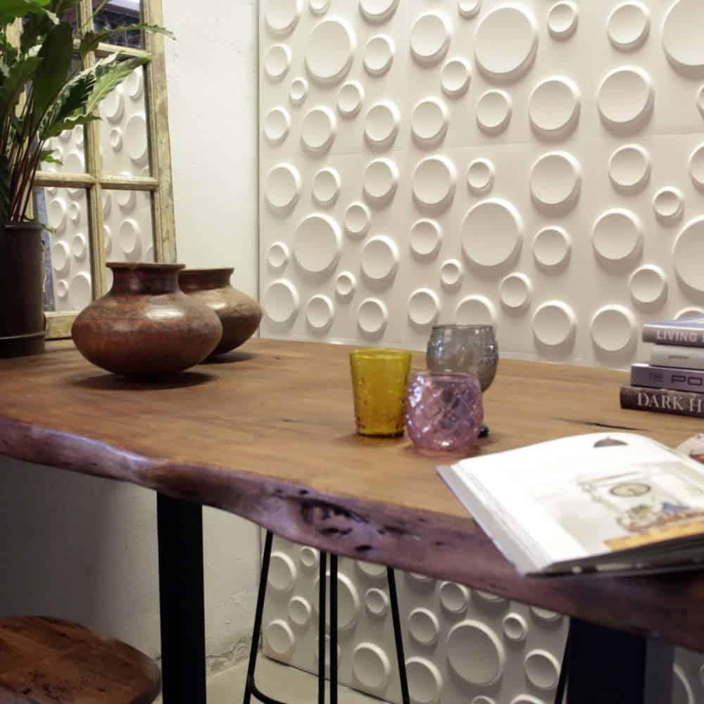 camera decorata cu panou decorativ alb, mobilata cu o masa din lemn si un ghiveci cu flori
