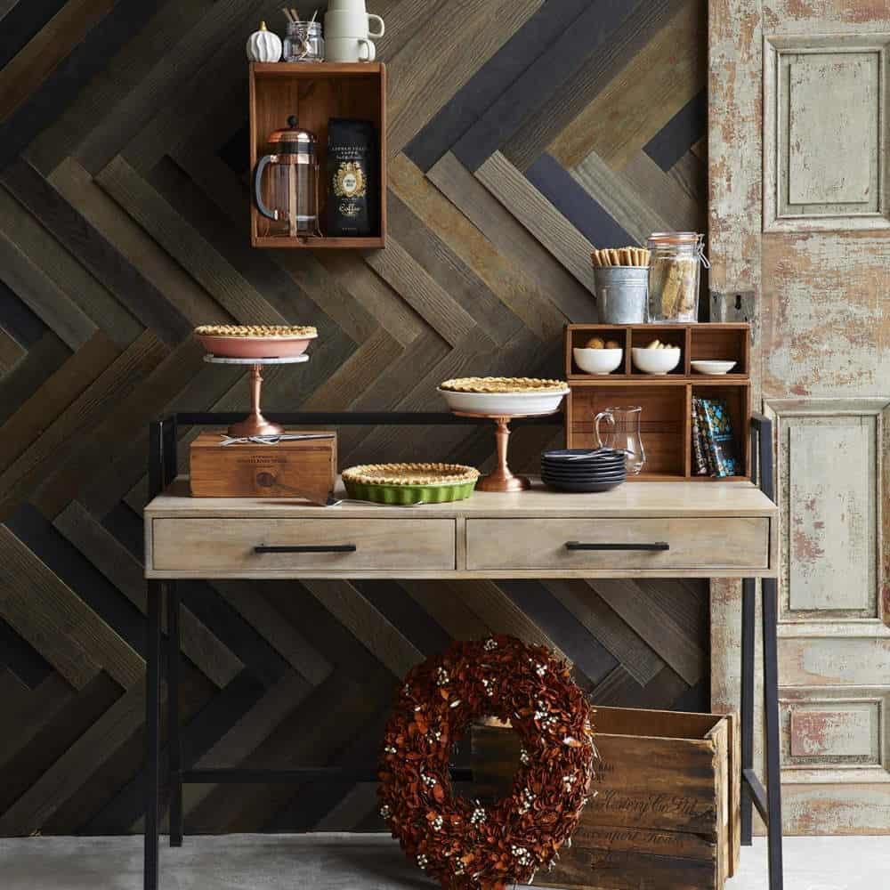 camera decorata cu panbou decorativ rustic de culoare maro si mobilata cu o masuta din lemn pe care sunt asezate farfurii cu placinta