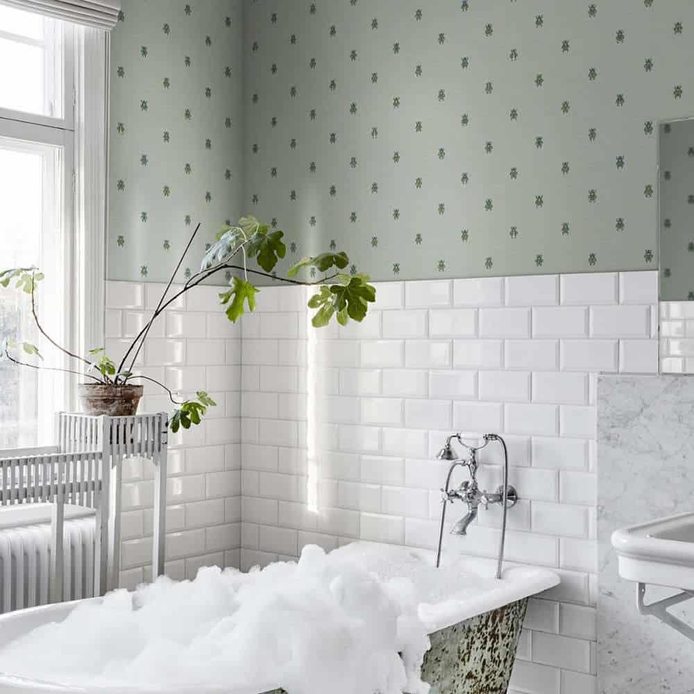 baie decorata cu placi de faianta albe si fototapet verde si mobilat cu o cada plina cu spuma