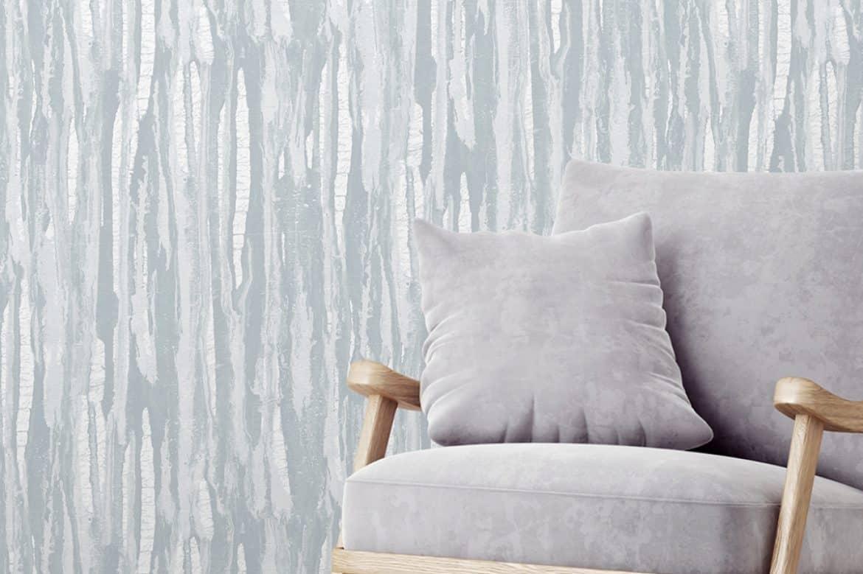 Perete cu tapet din fibră de sticlă de culoare gri cu dungi albe langă un fotoliu din tapiterie gri cu manere și picioare din lemn și pernuță decorativă gri