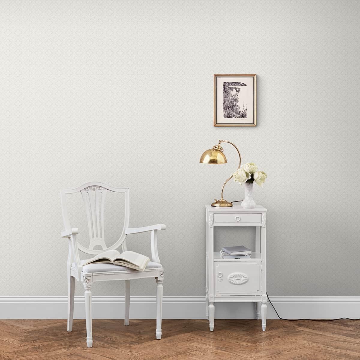 Scaun alb si noptiera alba aseste langa un perte cu tapet alb, pe care este asesta un tablou decorativ cu rama aurie