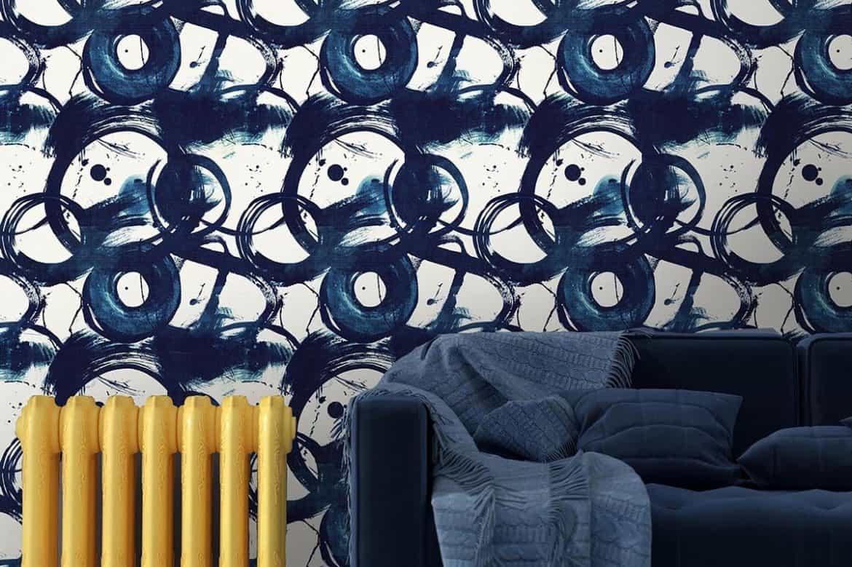 canapea de culoare albastra, langa un perete cu tapet albastru