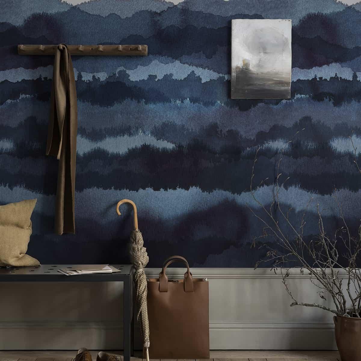 perete cu tapet vopsibil albastru pe care atarna un cuier din lemn si un tablou peisaj