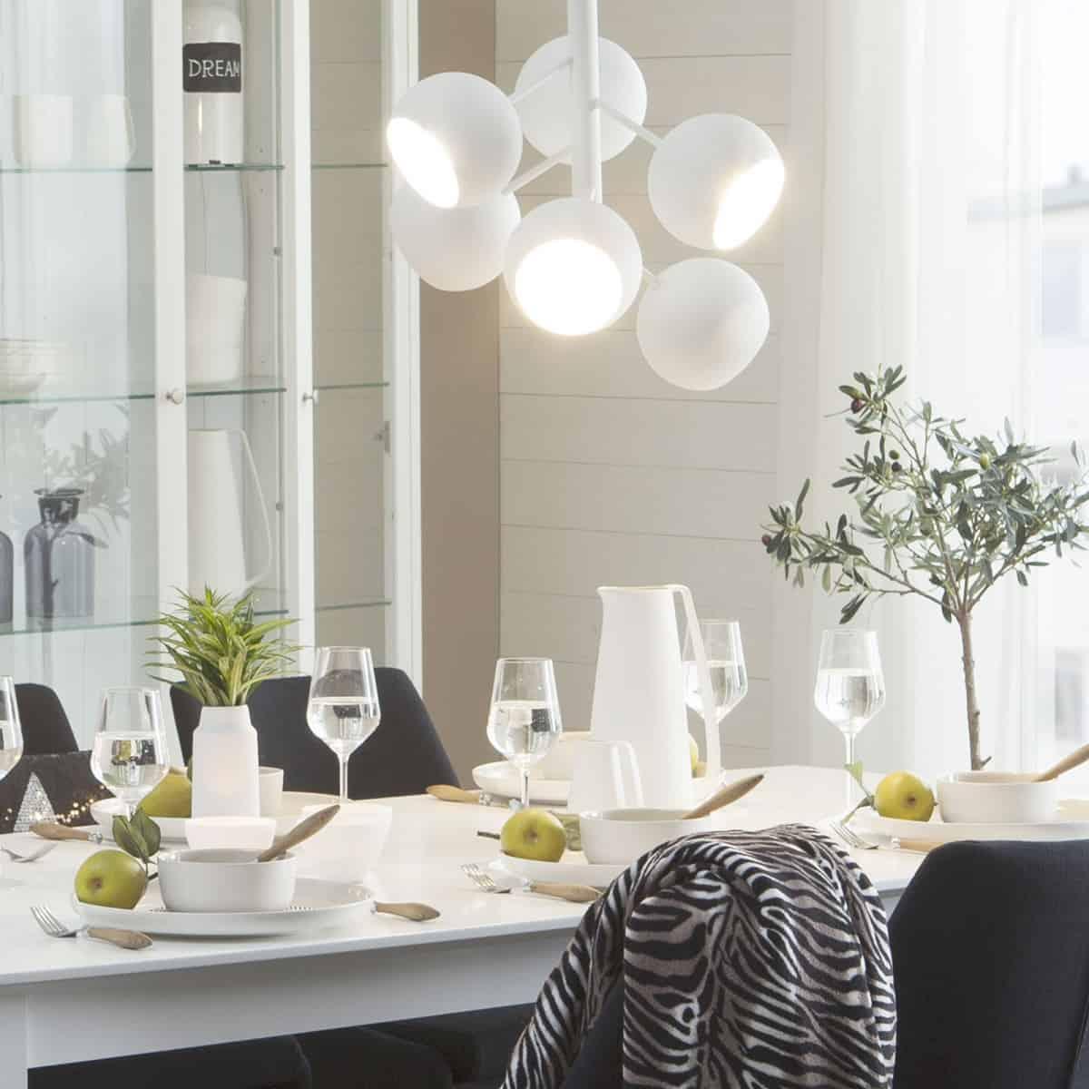 lustra suspendata alba cu sase globuri metalice asezata deasupra unei mese intr-o camera de dining decorata cu alb, crem, negru si verde