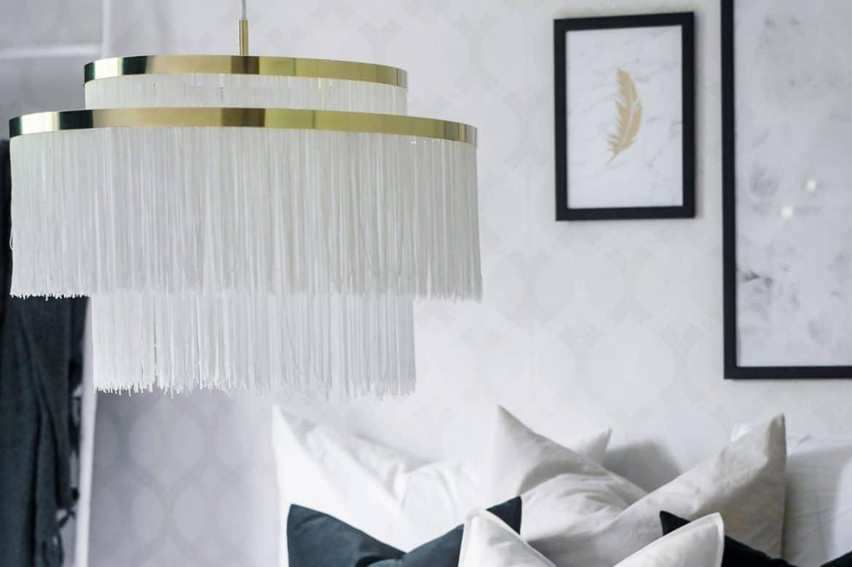 Lustra lux alba din material textil intr-un dormitor alb cu elemente de decor albe, negre si gri