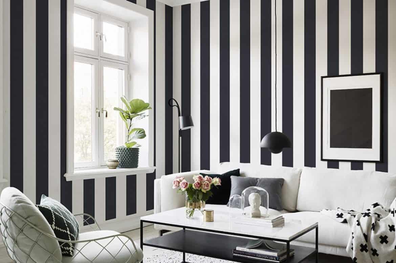 montare tapet lavabil in dungi late de culoare alb si negru intr-un living decorat in alb, negru si tonuri de gri