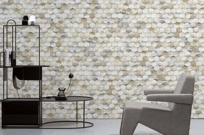 tapet mozaic forme geometrice intr-un colt de living cu fotoliu in stil futurist gri si raft metalic negru