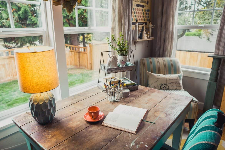 birou amenajat in fata unor ferestre imense intr-un living decorat in stil modern, cu lampa, cana si plante pe masa