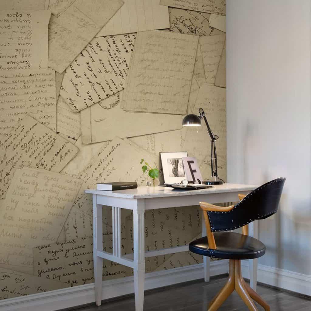 Fototapet cu scrisori vechi aplicat pe un perete in fata caruia se afla o masa de lucru si un scaun