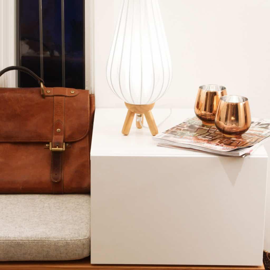 Lampa de birou cu abajur alb, asezata pe o masuta alba, langa reviste si vase decorative si o servieta