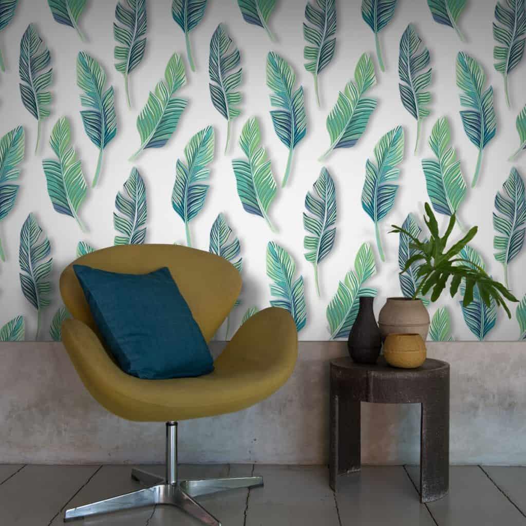Tapet cu frunze aplicat pe un perete in fata caruia se afla un fotoliu mustar, cu perna decorativa si o masa cu vase decorative si o planta