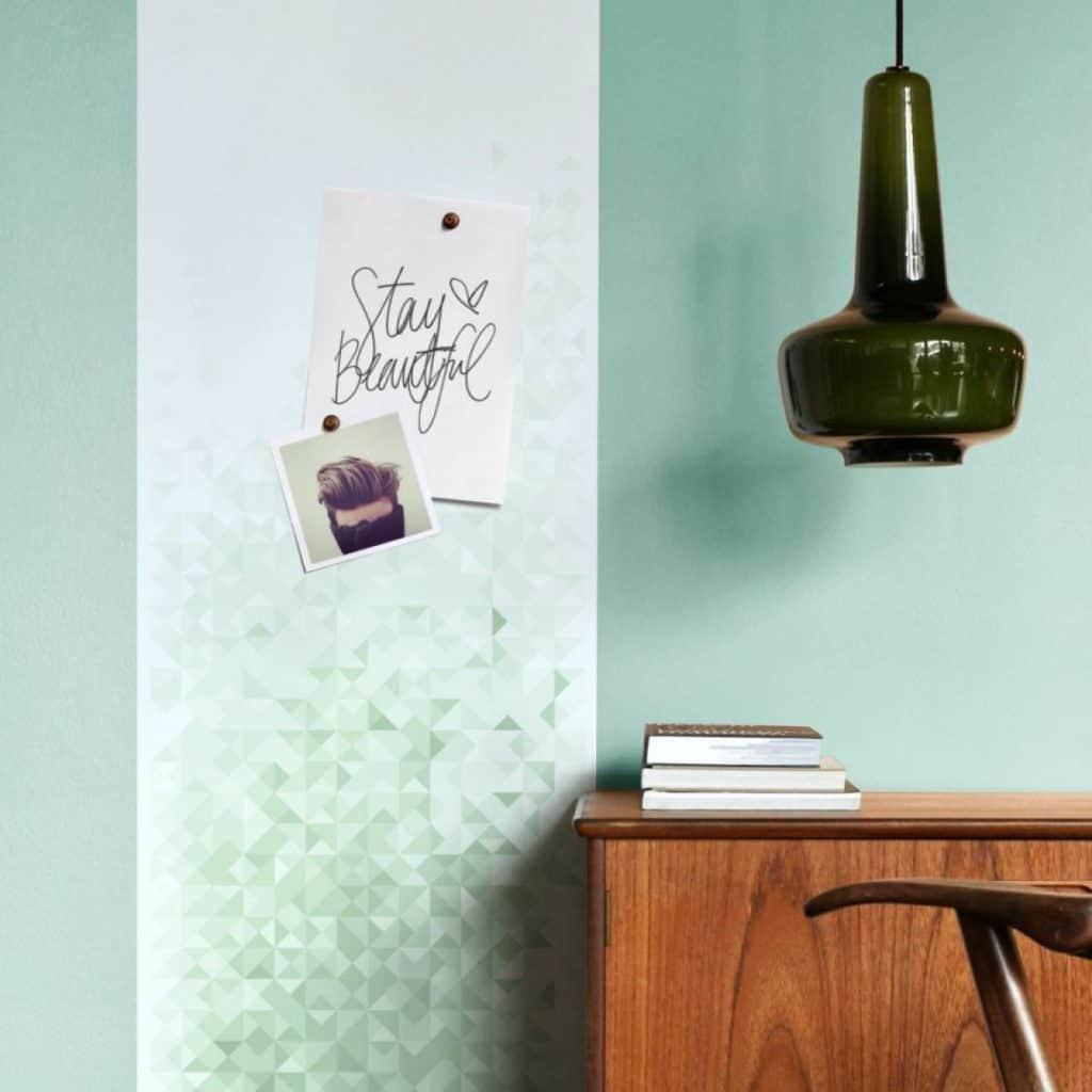 Tapet magnetic geometric verde cu doua fotografii, langa un birou din lemn pe care sunt asezate carti si un corp de iluminat suspendat