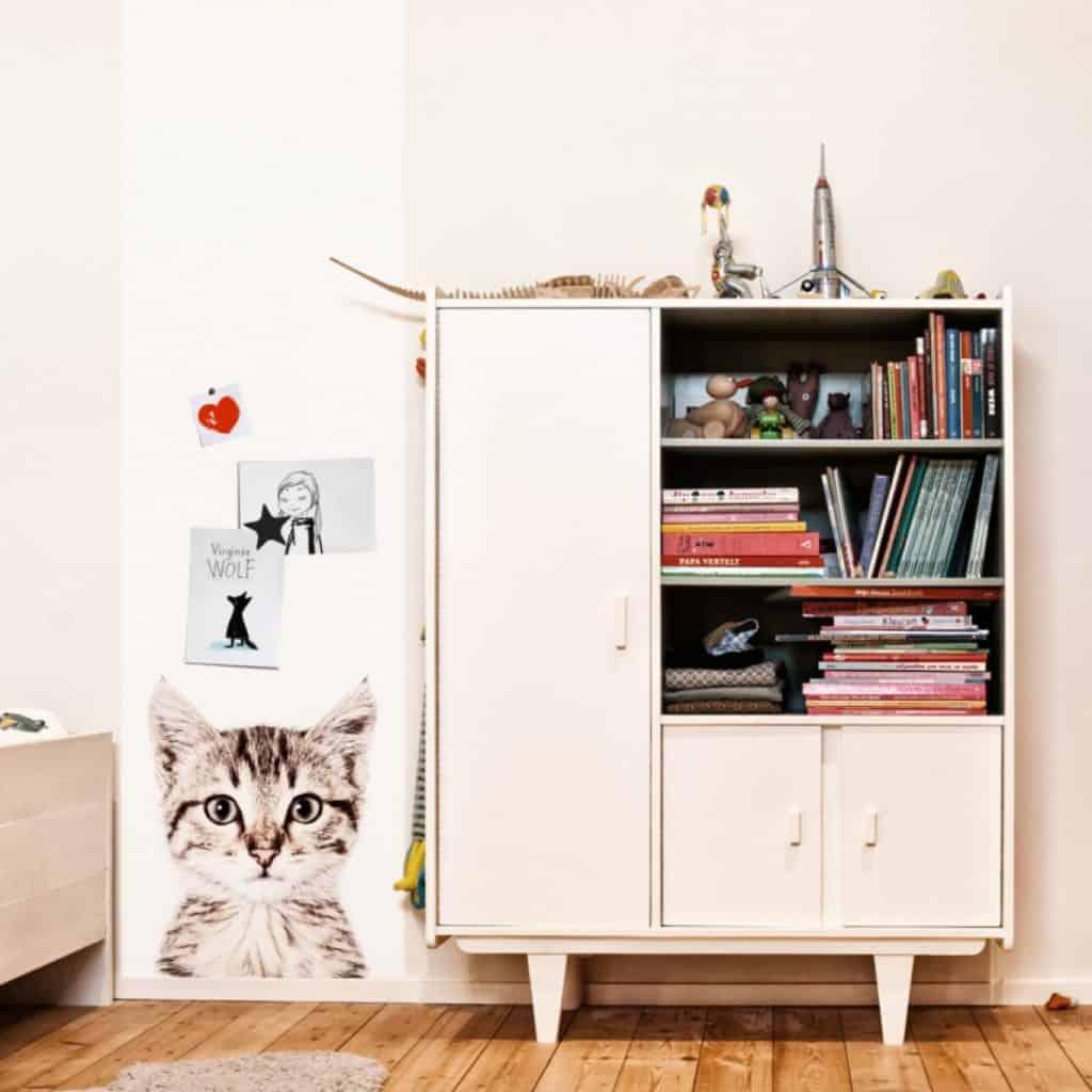 Tapet magnetic cu pisica aplicat pe un perete langa care se afla un dulap cu rafturi pentru carti