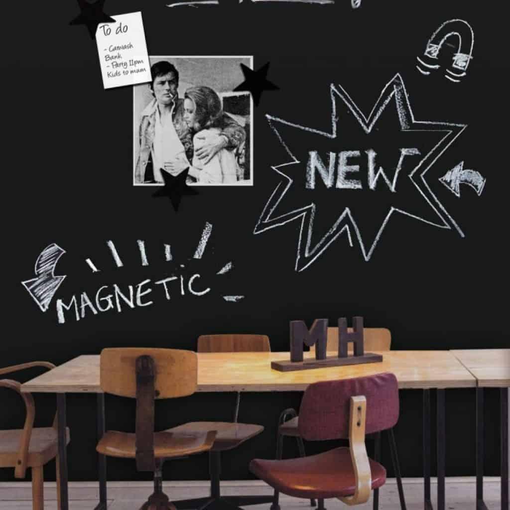 Tapet magnetic tabla de scris de culoare neagra, scris cu creta si cu o fotografie aplicata, in fata caruia este asezata o masa cu scaune