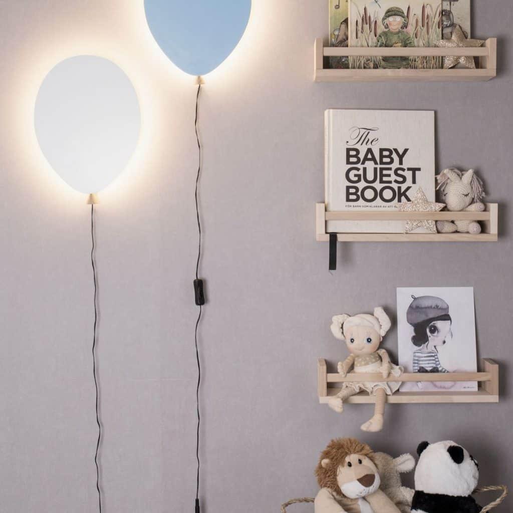 Aplice de perete sub forma de baloane albastre instalate langa etajere suspendate cu jucarii