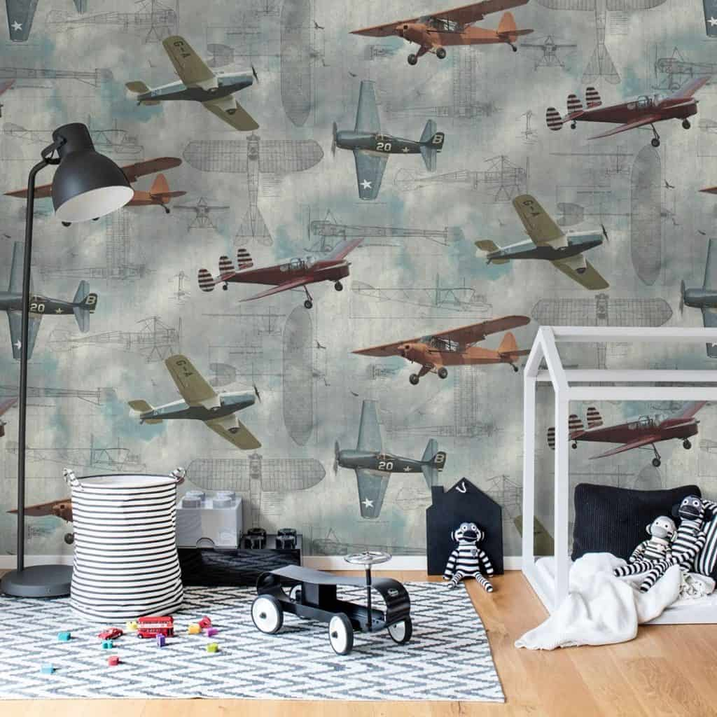 Perete decorat cu fototapet cu avioane intr-o camera cu jucarii si cu covor pe podea