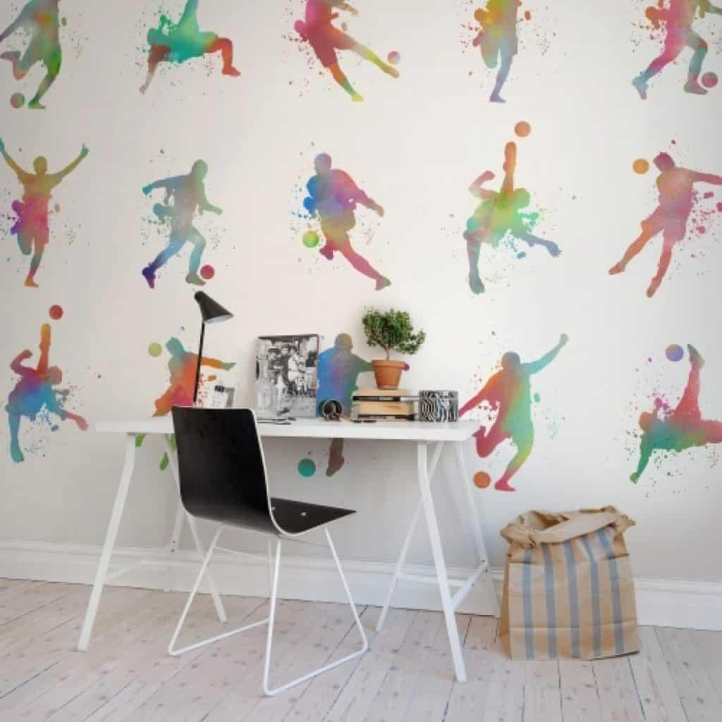 Perete decorat cu fototapet cu motive multicolore inspirate din sport, in fata caruia se afla o masa si un scaun