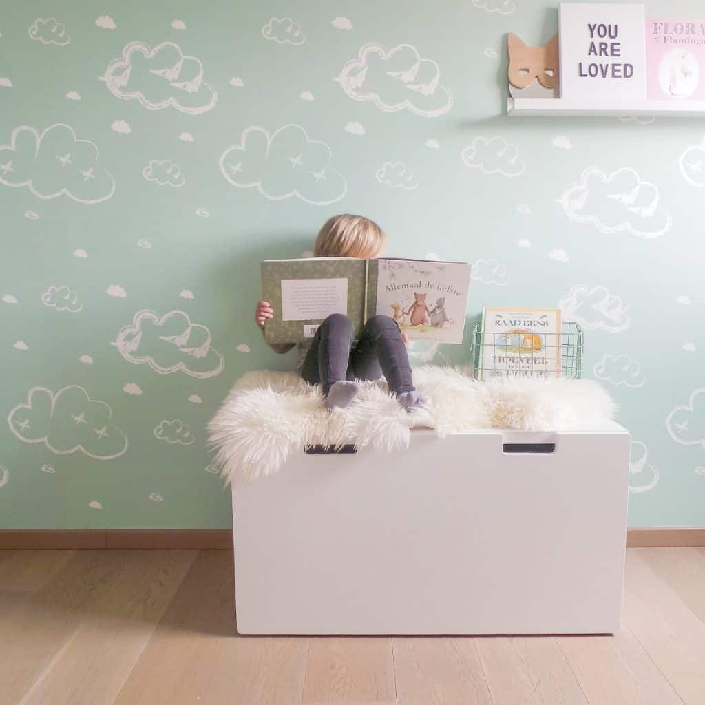 Perete decorat cu tapet cu norisori in fata caruia se afla un element de mobilier alb pe care sta un copil cu o carte in mana