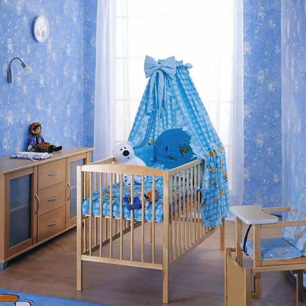 Camera bebelus cu pereti albastri, in mijloc cu un patut pentru copii și elemente de mobilier pe laterale