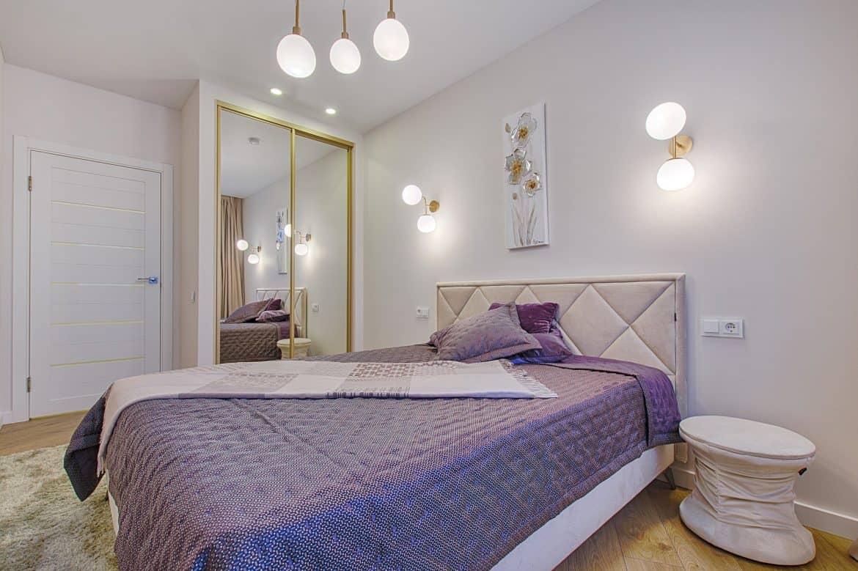 Dormitor cu pat in mijloc, dressing cu oglinzi, noptiera alba, tablou si corpuri de iluminat aplicate pe perete