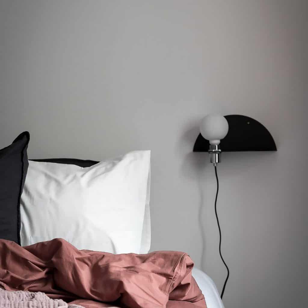 Aplica de perete intr-un dormitor cu pat, lenjerie violet și perna alba