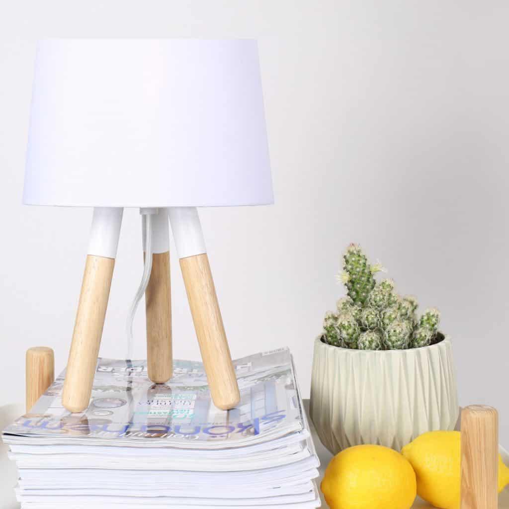 Lampa de noptiera cu picioare din lemn, alba, pe un teanc de reviste asezata langa o planta decorativa si lamai