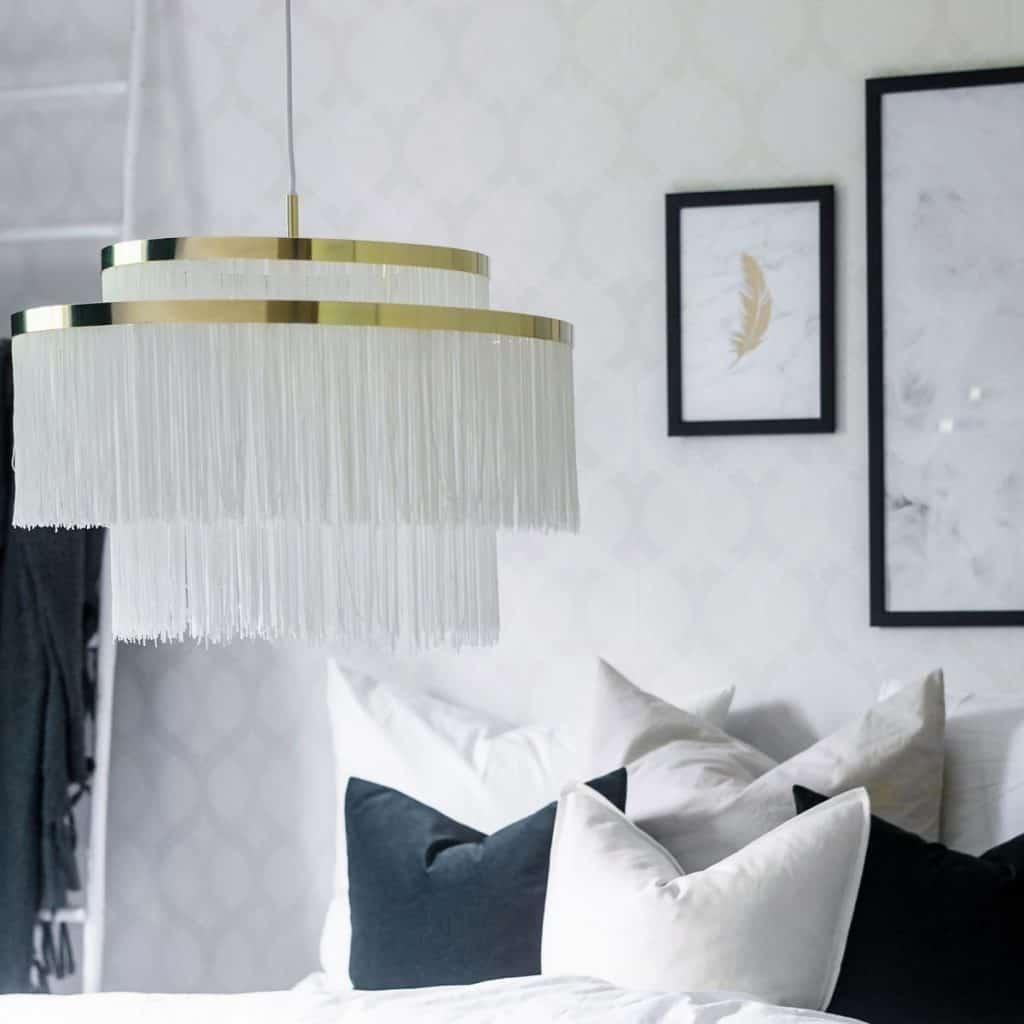 Lampa suspendata cu franjuri textile albe intr-un dormitor cu pat si perne decorative si doua tablouri pe un perete