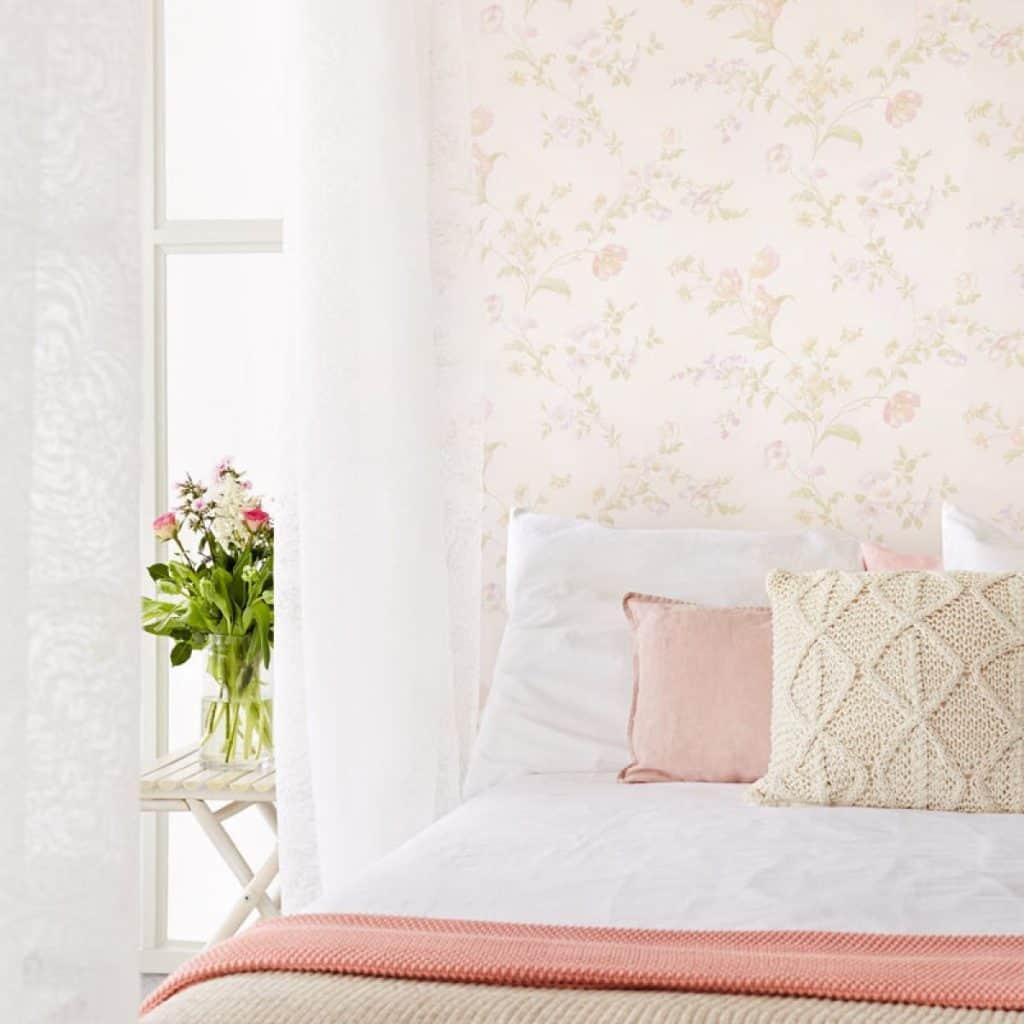 Dormitor amenajat cu tapet cu imprimeu floral in culori discrete, cu pat si perne decorative
