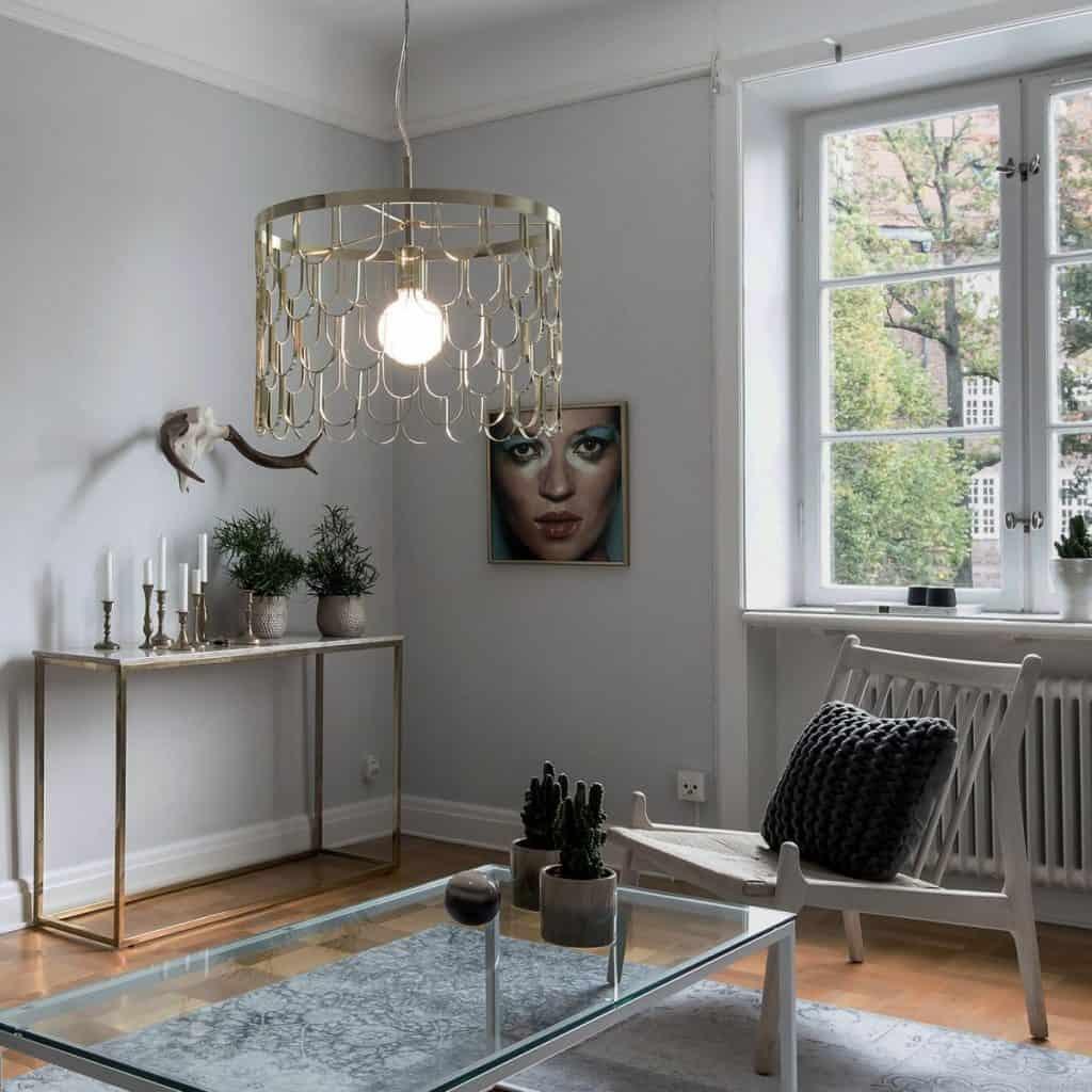 Lampă metalică suspendata intr-o camera amenajata cu masa de cafea din sticla, scaun si masa cu elemente decorative