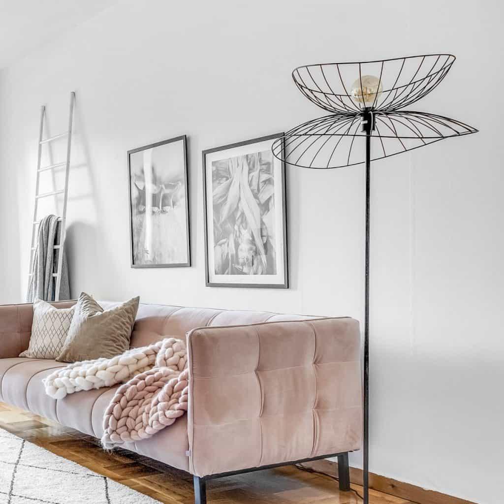 Lampadar asezat langa o canapea deschisa la culoare, in fata unui perete alb cu doua tablouri si scara