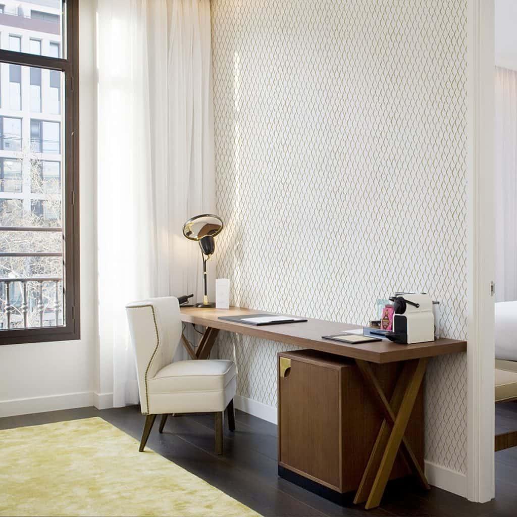 Perete intr-o camera amenajat cu tapet crem, in fata caruia se afla un birou din lemn si scaun alb, pe o podea inchisa la culoare, pe care se afla un covor in nuante deschise