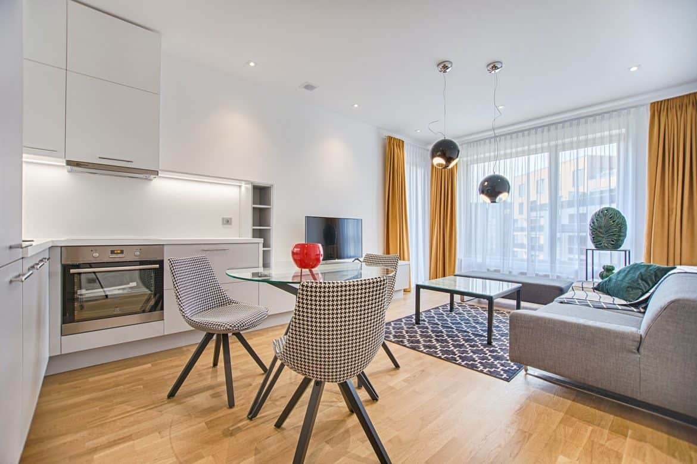Garsoniera open space cu canapea, masa de cafea și bucatarie cu masa si scaune