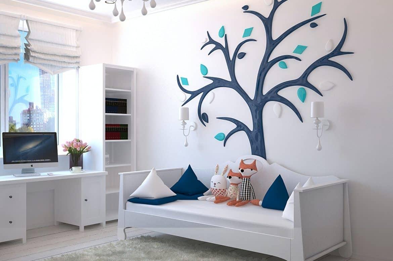 Camera unui copil cu mobilier alb, perete decorat cu un copac si covor