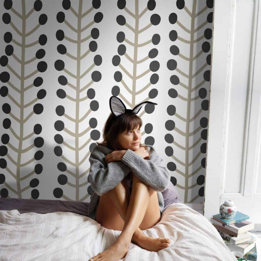Perete amenajat cu fototapet in fata caruia se afla o tanara asezata pe pat